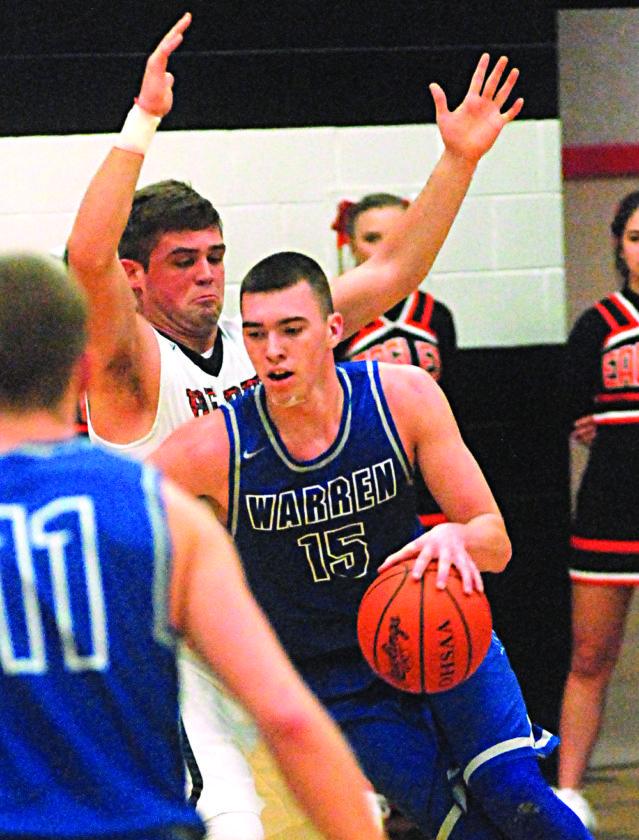 STEVE HEMMELGARN The Marietta Times Warren's Josh Huffman (15) handles the ball as Belpre's Bailey Sprague defends during a high school boys basketball game Tuesday in Belpre.