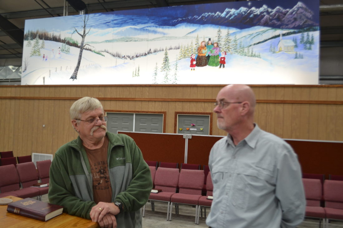 Artist Roger Bonnette and Pastor Carl Kesselring talk in the sanctuary of the Waterford Church of the Nazarene below the mural Bonnette painted for the church.
