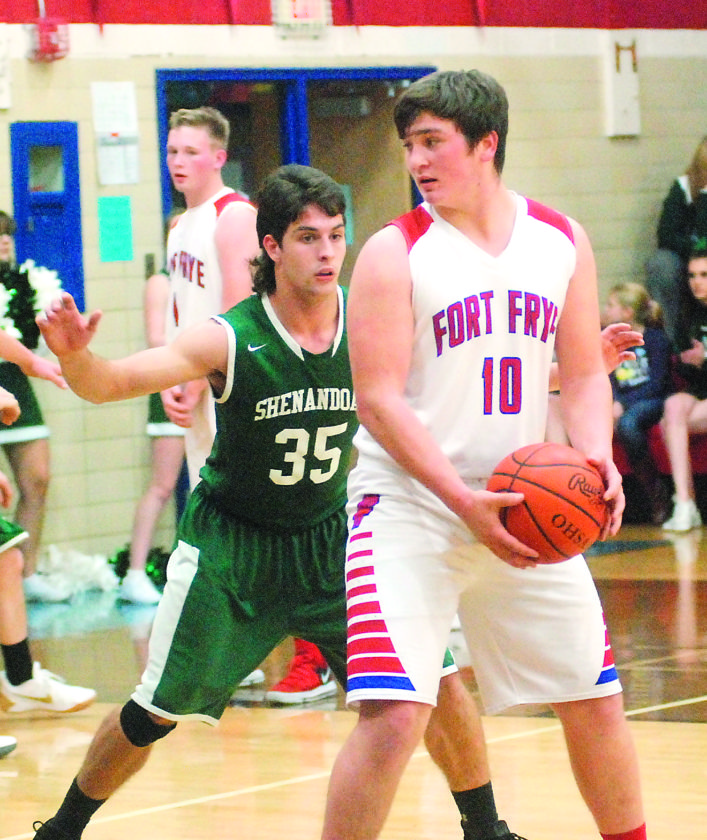 Fort Frye's Tyler Bradford (10) holds the ball as Shenandoah's Chase Chicwak defends during a high school boys basketball game last week in Beverly. Several local prep hoops teams are reaching an important part of their regular season schedule over the next two weeks.  JORDAN  HOLLAND The Marietta Times