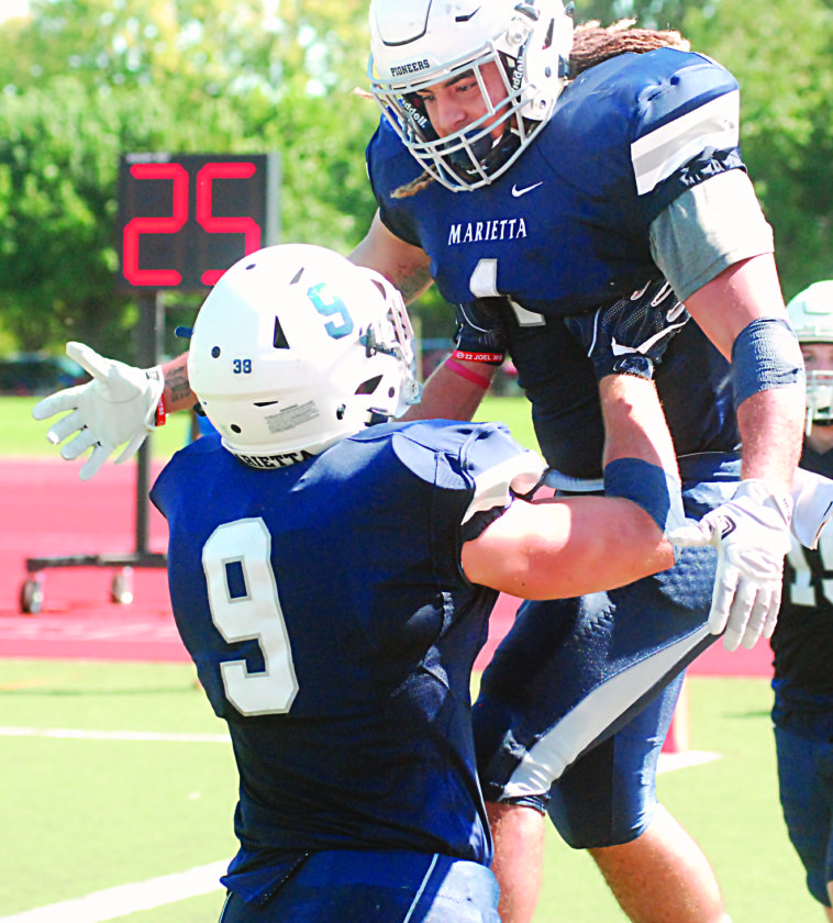 JORDAN HOLLAND The Marietta Times Marietta's College's Roger Walker (1) celebrates with teammate Tanner Clark (9) after a touchdown against Muskingum during a college football game earlier this season at Don Drumm Stadium.