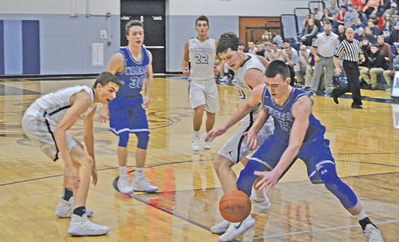 Warren's Josh Huffman, right, and Morgan's Marty Sidwell battle for the ball during a high school boys basketball game Saturday in McConnelsville. Photo by Mike Morrison.