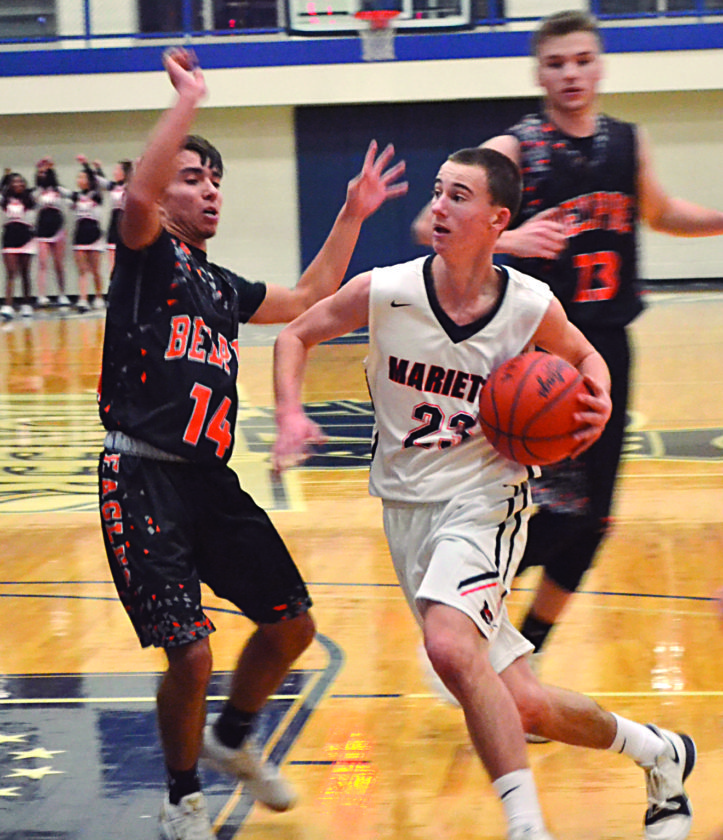 Marietta's Mark Duckworth II, right, drives to the basket as Belpre's Logan Adams defends during a game Friday at Ban Johnson Arena in Marietta.  RON  JOHNSTON The Marietta Times