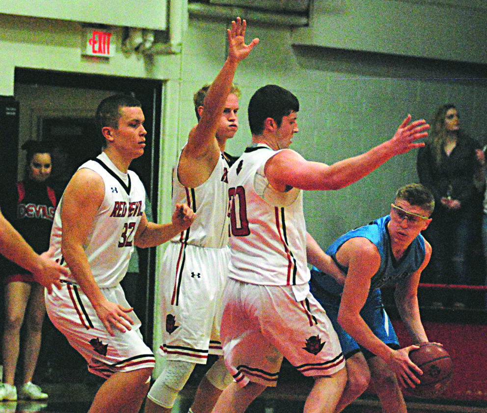JAY W. BENNETT The Marietta Times Parkersburg Catholic's Cade Ullman tries to make a pass into the paint during Friday night's game at Ravenswood as Red Devils Jayden Rhodes (10), Isaiah Morgan (20) and Chase Swain (32) defend.