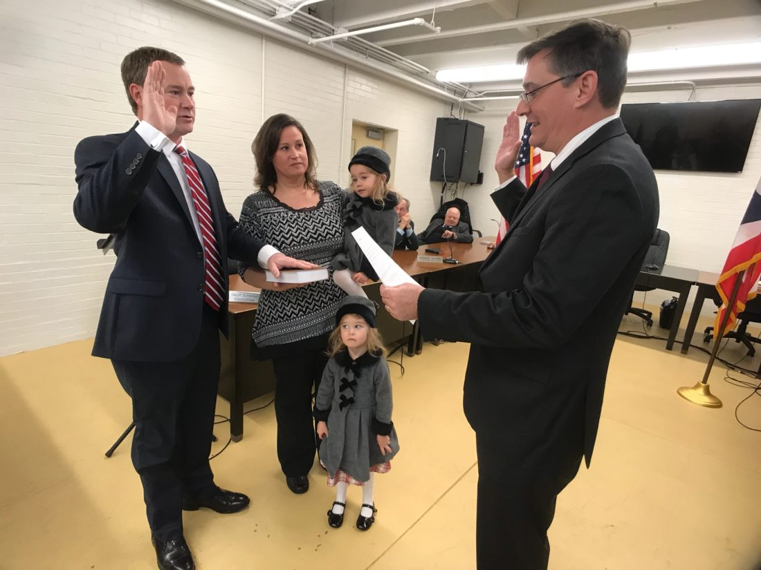 JANELLE PATTERSON   The Marietta Times Joshua Schicher, left, stands with his family as Washington County Common Pleas Court Judge Mark Kerenyi swears Schlicher in to another term as President of Marietta City Council.