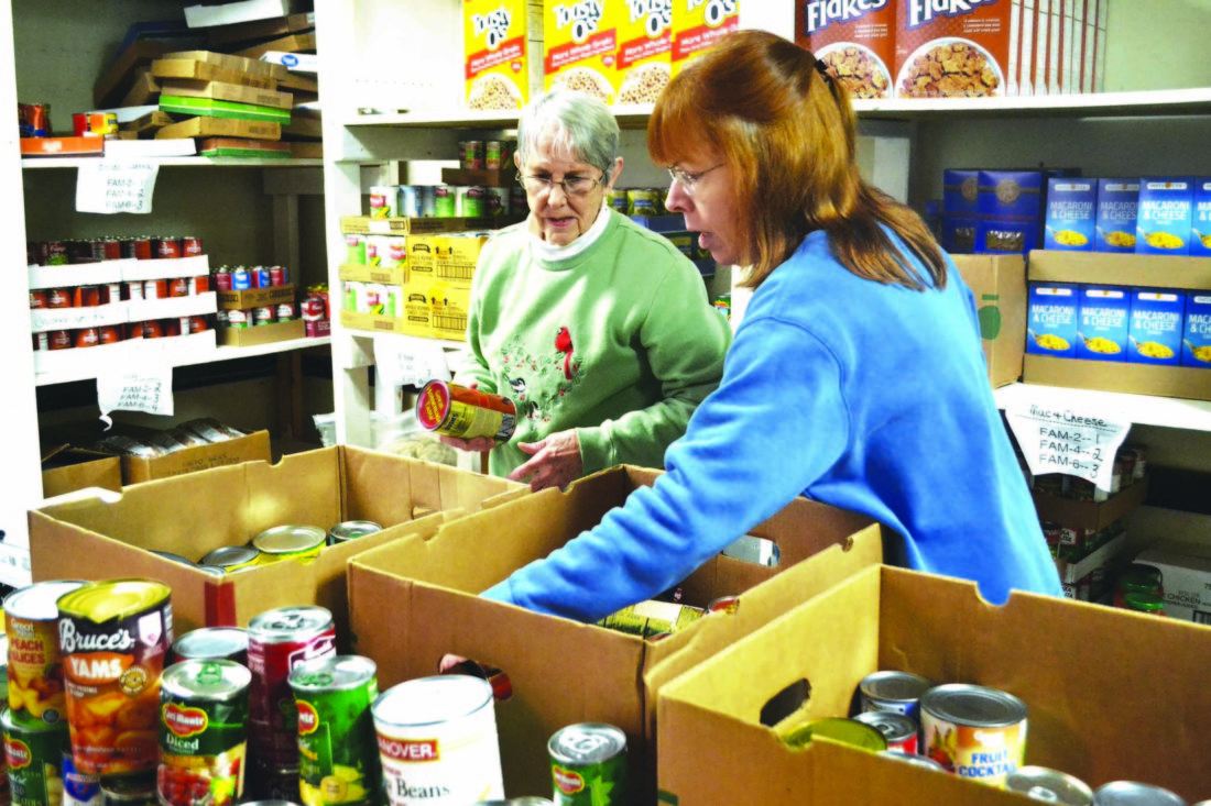 ERIN O'NEILL  The Marietta Times Longtime volunteer Judy Fritsche, left, and Marietta Community Food Pantry director Laurie Nash, right, stock shelves with a large donation received at First Congregational Church Tuesday. After the holidays, area food pantries experience a slump in donations while the need is just as great.