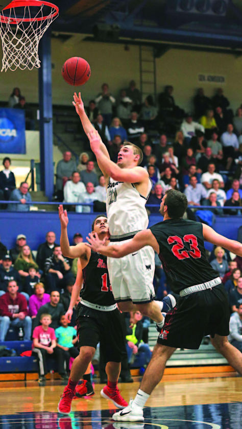 Photo courtesy of Rebecca Wheeler Marietta College's Kyle Dixon (21) goes up for a basket during a college men's basketball game against Muskingum Wednesday at Ban Johnson Arena. Marietta won, 104-86.