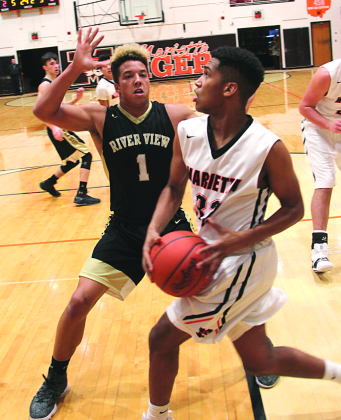 TOM PERRY The Marietta Times Marietta High's Tony Munos (32) drives with the ball as River View's Keith Stewart (1) defends during a high school boys basketball game Friday at Sutton Gymnasium.