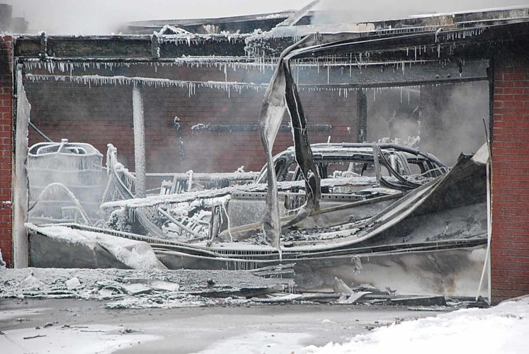 Art Smith   The Marietta Times Ice hangs off a truck and garage following a fire Wednesday morning at a 516 Middle St. home in Belpre.