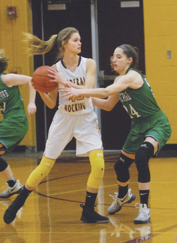 JORDAN HOLLAND The Marietta Times Federal Hocking's Emma Beha (45) looks to pass as Waterford's Megan Ball defends during a high school basketball game Thursday in Stewart. Waterford won, 55-23.