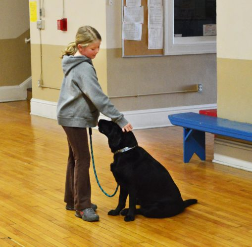 DOUG LOYER  Special to the Times Sophia Linscott, 10, of Marietta pats her dog Olive, a Black English Labrador, on the head after completing a trick.