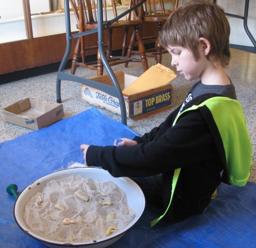 "Gabe Sheehy, of Marietta, works on a hands-on activity at the annual Campus Martius Museum ""Digging the Past Archaeology Day"" on Saturday."