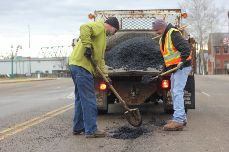 JANELLE PATTERSON   The Marietta Times Kevin Francis and Vince Jett shovel cold mix into a pothole on Second Street Tuesday.