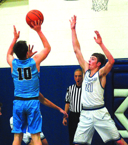 JAY W. BENNETT The Marietta Times Warren's Troy Huck, who finished with 15 points including a slam dunk in the second quarter during the Warriors' 67-42 win against visiting Parkersburg Catholic on Thursday night, challenges a shot in the paint by Crusader Jeb Boice.
