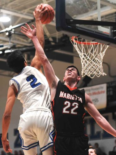 Photo courtesy of Sam Blackburn Marietta's Austin Witucky goes up for a block against Zanesville's Cameron Brooks-Harris during Friday's game.