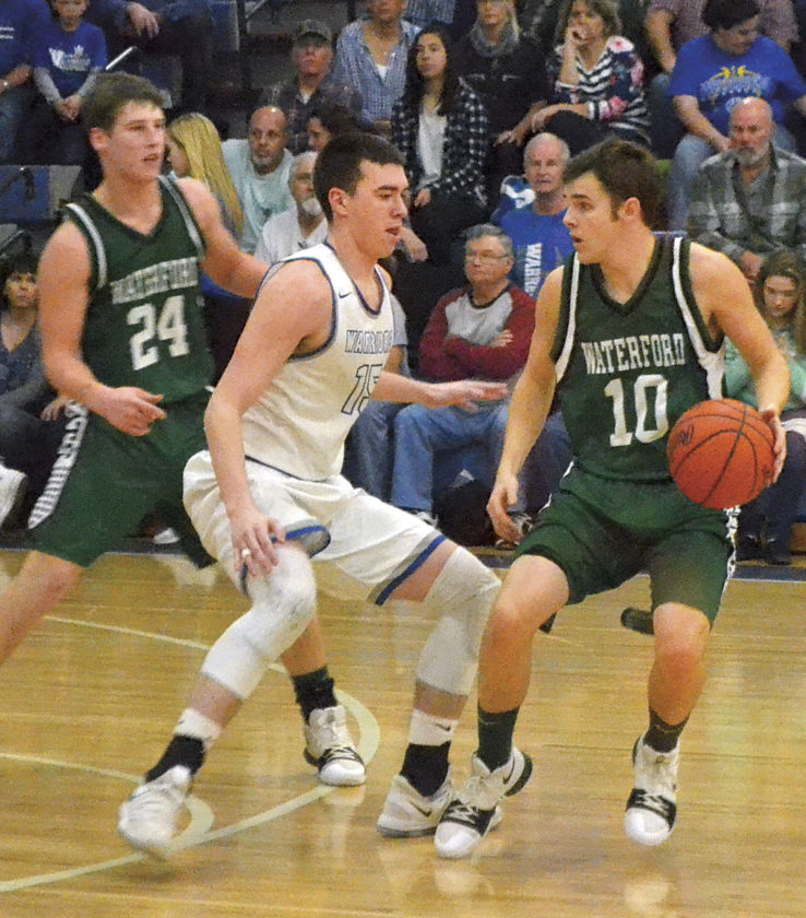 MIKE MORRISON The Marietta Times Warren's Josh Huffman (15) guards Waterford's Austin Pyatt during a high school boys basketball game Saturday in Vincent.