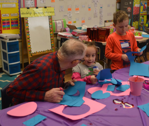 ERIN O'NEILL  The Marietta Times Glenwood resident Bob Oliver, left, gets some assistance Tuesday with his Valentine craft from Phillips Elementary School first-graders Maddy Patterson and Levi Prim, right.