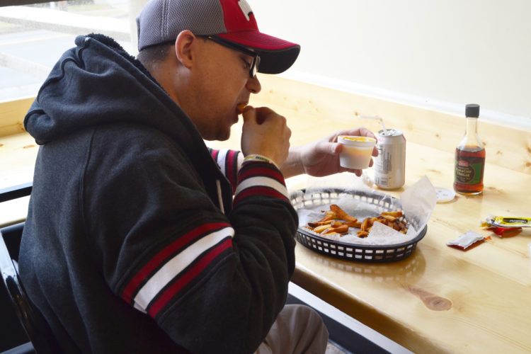ERIN O'NEILL  The Marietta Times Marietta resident Mike Sauer enjoys fresh cut fries with cheddar cheese dip as he visits Flying Dogs Hot Dogs, the newest eatery to occupy the building at 281 Seventh St.