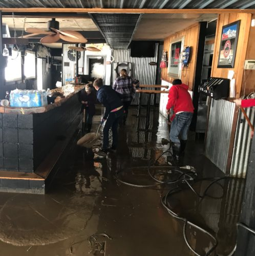 JANELLE PATTERSON   The Marietta Times Volunteers and staff push out mud and water inside Boathouse BBQ on the city's west side Monday as flood waters from the Ohio River leave behind a mess.