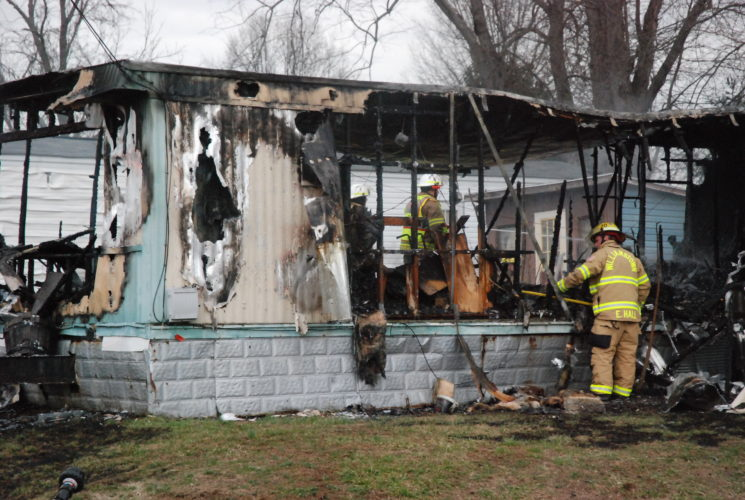 Evan Bevins   Special to the Times A Williamstown volunteer firefighter sifts through the debris at a 147 Onward Road, Boaz, trailer that burned Monday afternoon. Two occupants of the home were taken to Marietta Memorial Hospital.