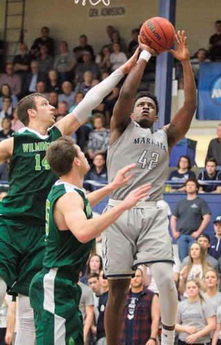 Photo courtesy of France Moise Marietta College's Avery Williams (42) attempts a shot during an Ohio Athletic Conference Tournament quarterfinal matchup against Wilmington Tuesday at Ban Johnson Arena. Marietta won, 86-71.