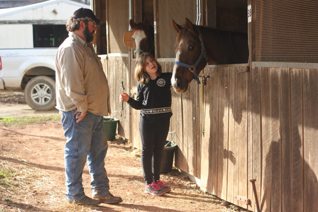 JANELLE PATTERSON   The Marietta Times Washington County Fair Board Member Dan Mason and his step-daughter Madison Biehl, 10,  check out Wednesday the horses moved to a higher barn on the fairgrounds prior to this weekend's flooding.
