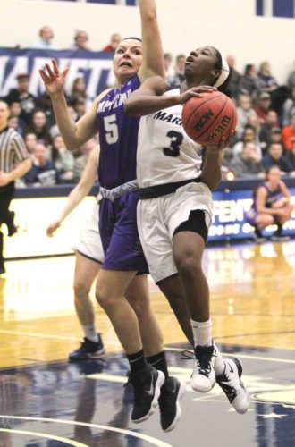 Photo courtesy of France Moise Marietta College's Amisha Herd, right, attacks the basket during Thursday's Ohio Athletic Conference Tournament semifinal against Capital at Ban Johnson Arena.