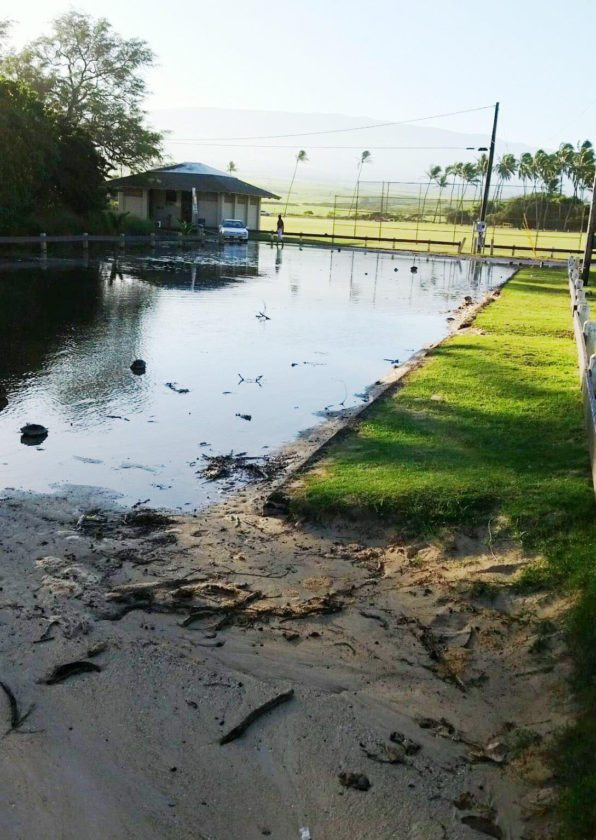 A pond of water is left in a Baldwin Beach Park parking lot on Thursday. High surf closed the park until further notice, county officials said. Maui County photo