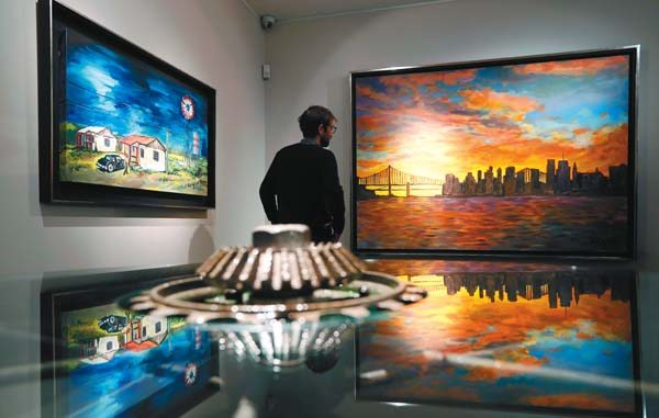 "A man gazes at a painting by Bob Dylan called ""New York Skyline, seen from Queens,"" with a piece called ""Threatening Skies"" at left, both reflected in an artwork called ""Ironwork Table."" The exhibition called ""Bob Dylan The Beaten Path"" opened Saturday at the Halcyon Gallery in London and runs until Dec. 11. AP photo"
