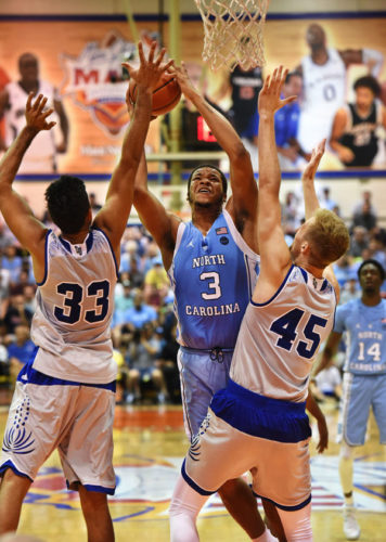 Kennedy Meeks of North Carolina attempts a shot against the defense of Chaminade's Kiran Shastri (left) and Nate Pollard during the first half of the Tar Heels' 104-61 win over the Silverswords on Monday. The Maui News / MATTHEW THAYER photo