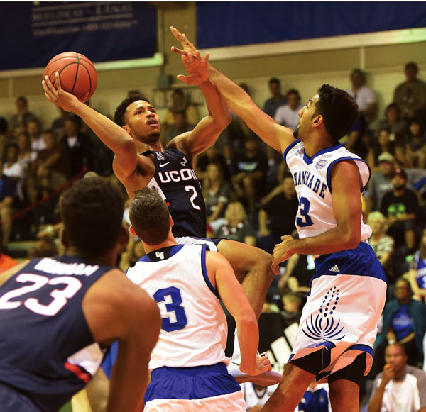 Connecticut's Jalen Adams tries to get off a shot over Chaminade's Kiran Shastri  during the first half of the Huskies' 93-82 win over the Silverswords on Tuesday. Looking on are UConn's Juwan Durham and Chaminade's Sam Daly. The Maui News / MATTHEW THAYER photo