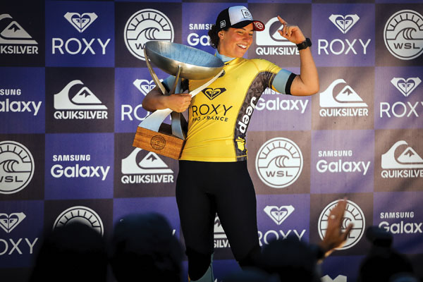 Tyler Wright celebrates with her trophy after securing the tour championship in October in France. WSL / Damien Poullenot photo