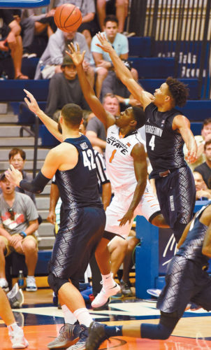 Oklahoma State's Jawun Evans gets between Georgetown's Bradley Hayes and Jagan Mosely for a layup in the first half of the Cowboys' 97-70 win over the Hoyas in Wednesday's third-place game. The Maui News / MATTHEW THAYER photo