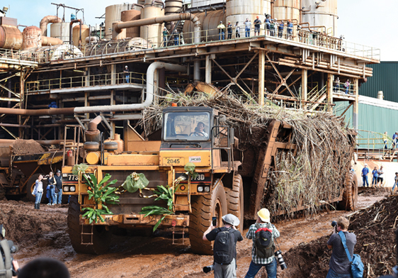 Hawaiian Commercial & Sugar Co. driver Fermin Domingo guides Maui's last load of harvested sugar cane to the Puunene Mill's unloading station Monday morning as employees, retirees, media and others capture the historic moment with their cameras. The Maui News / MATTHEW THAYER photo