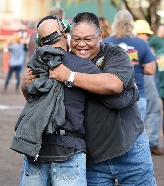 Former HC&S employees Teddy Espeleta (right) and Frank Nakoa greet each other before Monday's ceremony marking the last haul of sugar cane from the fields. The Maui News / MATTHEW THAYER photo