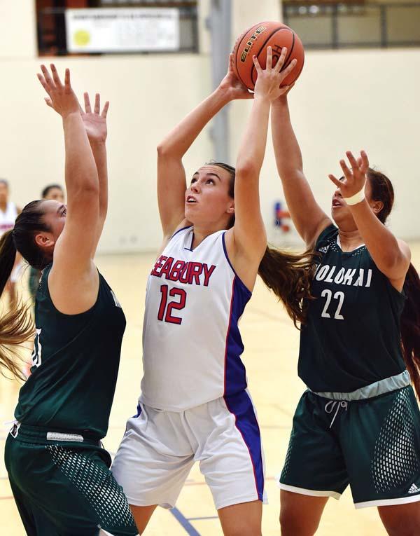 Seabury Hall's Makena Dougherty grabs a rebound between Molokai's Sydney Rawlins (right) and Brooke Keliihoomalu on Thursday. The Maui News / MATTHEW THAYER photo