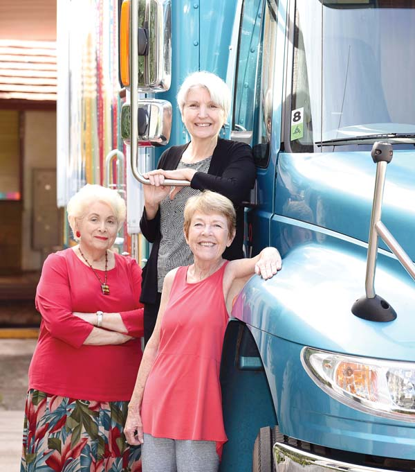 Dorothy Tolliver (from left), Susan Werner and Sara Foley pose with the new Holoholo Bookmobile they helped bring to Maui. They also got lawmakers to fund a librarian position for the bookmobile. The Maui News / MATTHEW THAYER photo