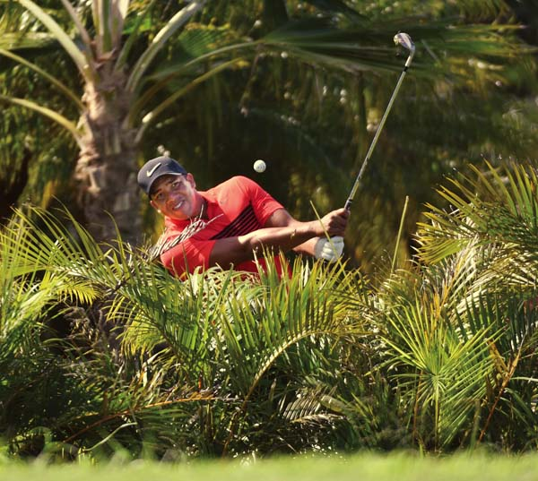 Jhonattan Vegas chips from the yard of a home adjacent to the Plantation Course's 14th hole — he managed to save par.    The Maui News / MATTHEW THAYER photo