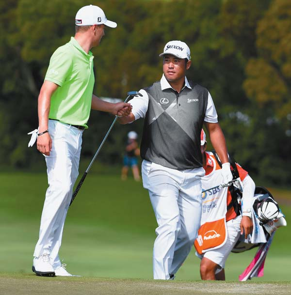 Hideki Matsuyama shares a fist-bump with playing partner Justin Thomas after chipping in for eagle on the Kapalua Plantation Course's 14th hole Sunday during the final round of the SBS Tournament of Champions. The Maui News / MATTHEW THAYER photo
