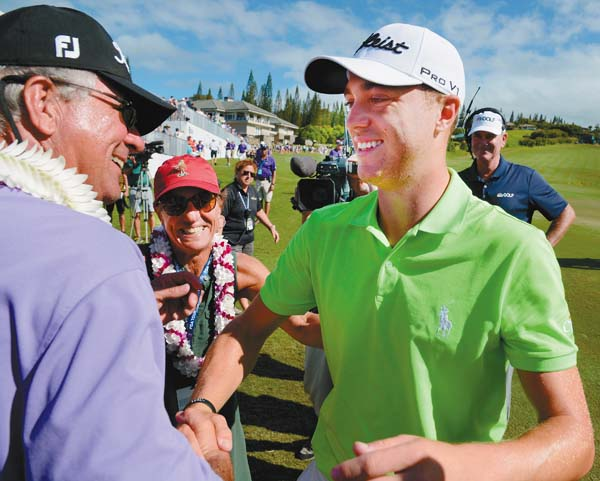 Justin Thomas celebrates with his parents Mike and Jani Thomas after his win in the SBS Tournament of Champions on Sunday at the Kapalua Plantation Course. The Maui News / MATTHEW THAYER photo