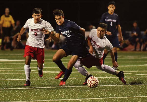 Aikala Chappell of Kamehameha Schools Maui is sandwiched by Lahainaluna's Erick Montiel (right) and Marcos Lopez in the first half of the teams' 0-0 draw Thursday night at Kanaiaupuni Stadium. The Maui News / MATTHEW THAYER photo