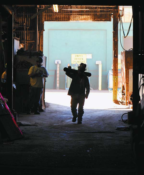 A worker carries a length of pipe through Puunene Mill.  The Maui News / MATTHEW THAYER photo