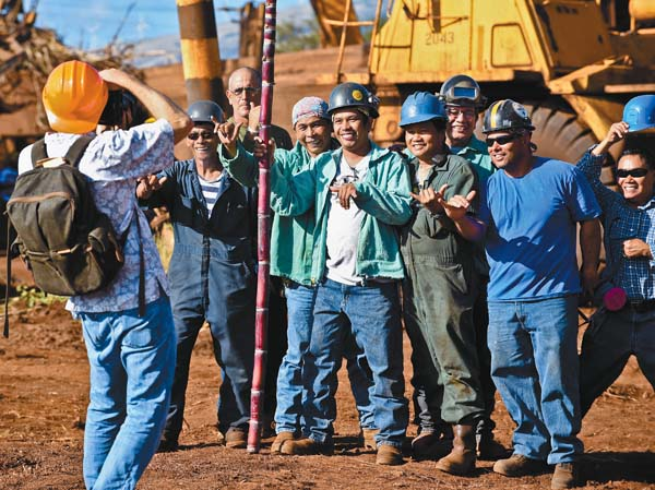 Members of Puunene Mill's welding crew pose with a stalk of cane after the conclusion of a brief blessing ceremony marking the start of Hawaiian Commercial & Sugar Co.'s 144th and last sugar harvest. Holding the stalk is Loreto Cabalse.  The Maui News / MATTHEW THAYER photo