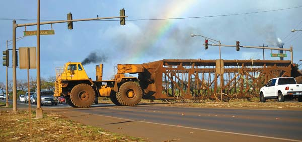 A tournahauler slips across Mokulele Highway to pick up another load of sugar cane.  The Maui News / MATTHEW THAYER photo