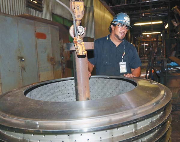 Millwright specialist Koa Martin stands next to a high-grade sugar basket inside Hawaiian Commercial & Sugar Co.'s Puunene Mill.  The Maui News / CHRIS SUGIDONO photo