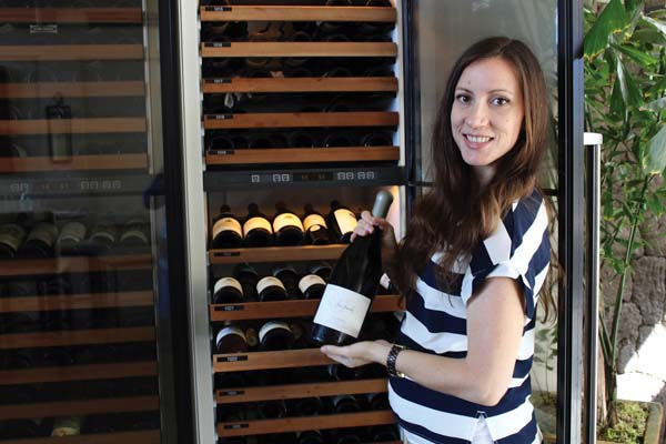 The Banyan Tree's manager Annie Harnish showcases a bottle from the cellar, 50 percent off on Wine Wednesdays.