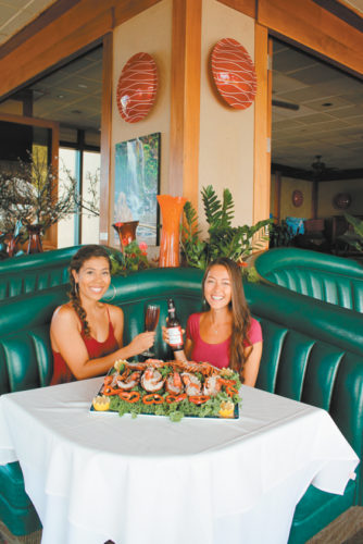 5 Palms at Mana Kai Resort in Kihei will heat things up with a romantic repast Tuesday on Valentine's Day. Hostess Raquel Tosaya (left) and server Lisa Levang get ready for the occasion. • The Maui News / CARLA TRACY photo