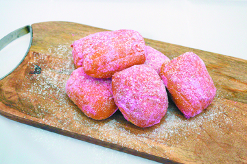 Woo your sweetheart with cream-filled, guava-flavored malasadas hot from the oil and rolled in powdered sugar. • Photo courtesy Home Maid Bakery
