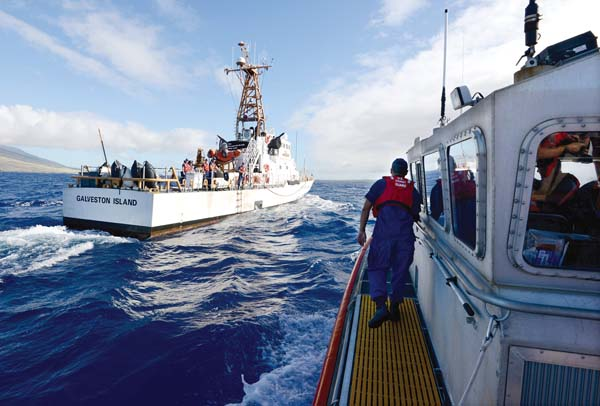 Crew members from U.S. Coast Guard Station Maui prepare to transfer passengers to the Oahu-based cutter Galveston Island on Tuesday morning. The crew and Ed Lyman, large whale entanglement response coordinator with the Hawaiian Islands Humpback Whale National Marine Sanctuary, were taking part in a patrol that's part of Operation Kohola Guardian, a program to protect both the massive marine mammals and oceangoers.  The Maui News / MATTHEW THAYER photo