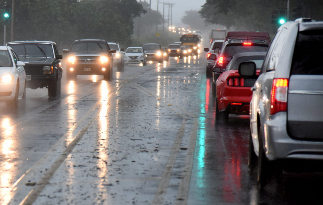 Traffic on Honoapiilani Highway emerges from a curtain of heavy rain Wednesday afternoon as it nears Lahaina. Stormy conditions forced drivers to slow to a crawl while passing through Launiupoko and Olowalu. • The Maui News / MATTHEW THAYER photo