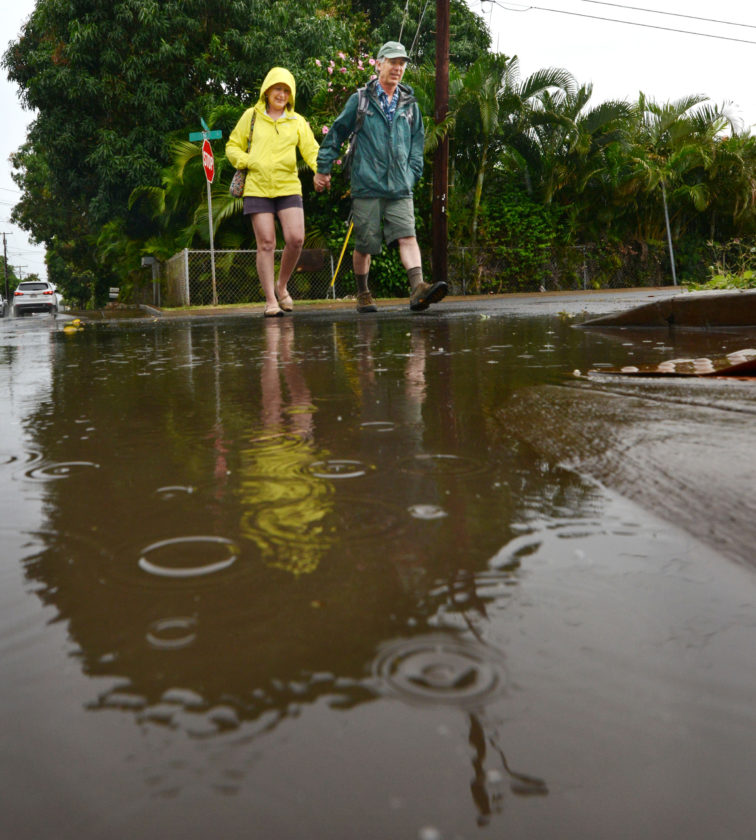 "Cathee and Bob Alex of Watertown, Conn., navigate around a large puddle while returning to Lahaina on Wednesday after walking to Kaanapali's Black Rock and back. On Tuesday, thinking it ""would be a good day to see waterfalls,"" the couple drove around the entire island, starting by circling the West Maui Mountains and continuing on to circumnavigate Haleakala. ""Maui is moody,"" Cathee said. ""But we would be in snow if we were in Connecticut.""  • The Maui News / MATTHEW THAYER photo"